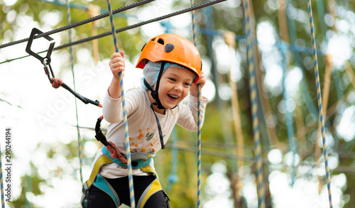 Poster Attraction parc Little girl in helmet climbs ropes in adventure park outdoors. Extreme sport, active leisure on nature.