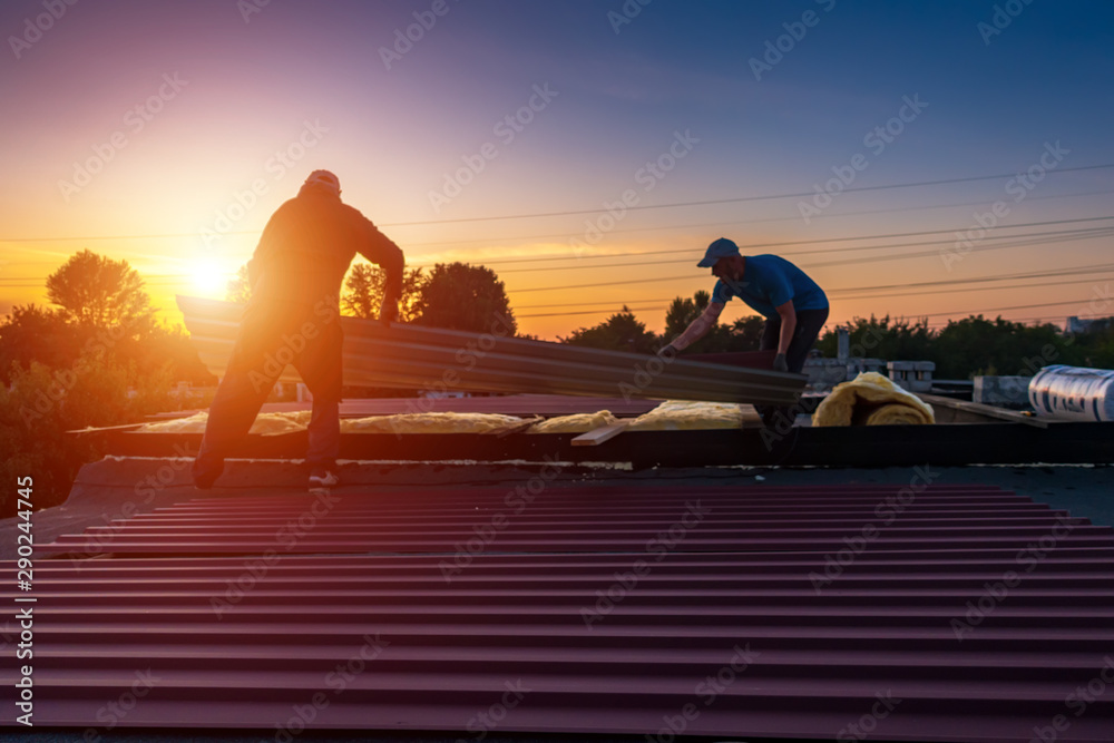 Fototapety, obrazy: A man holds a board on the roof. Men mount the roof on the building. People are blurred. Focus at the beginning of the picture
