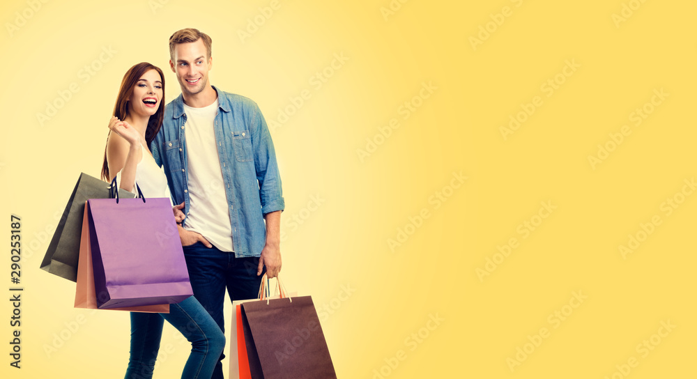 Fototapeta Photo of excited lovely couple with shopping bags, over yellow color background