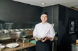 Portrait of Asian young cook holding bowl with salad and smiling at camera while standing in the kitchen of the restaurant
