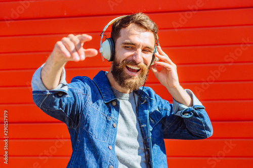 Portrait Expressive Smiling Guy Listening to Music. Young Ginger Guy in Grey Casual TShirt shows gesture rock sign. Isolated on Orange Background. Concept of Humans Emotions - 290257979