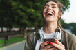 canvas print picture - Image of laughing woman holding smartphone and walking in green park