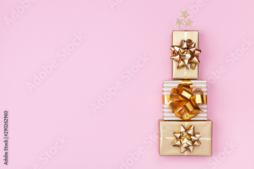 Canvas Prints Trees Stack of golden gift or present boxes in the form of Christmas tree on pink background top view. Celebration Christmas or New year concept. Flat lay.