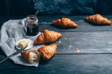 Croissants, Plum Jam And Butter On Dark Wooden Table With Copyspace
