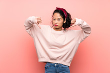 Asian Young Woman Over Isolated Pink Background Showing Thumb Down