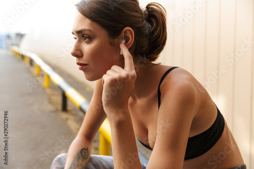 Image of charming young woman listening music with earpod - 290272946
