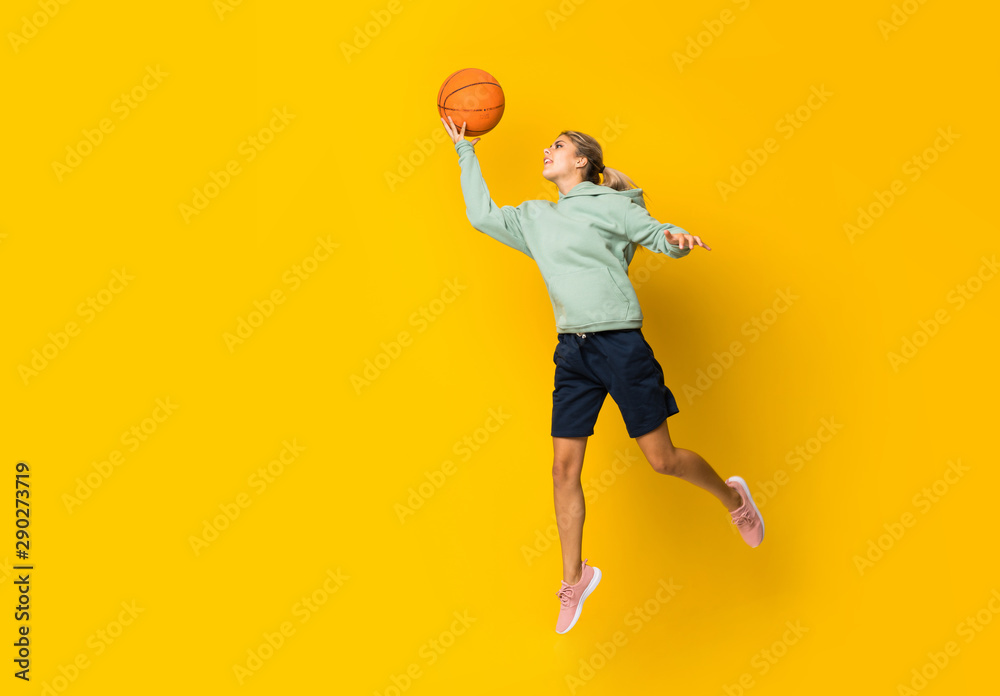 Fototapety, obrazy: Teenager girl basketball ball jumping over isolated yellow background.