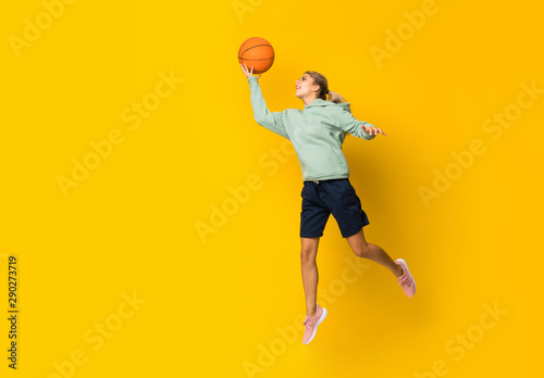 Teenager girl basketball ball jumping over isolated yellow background.