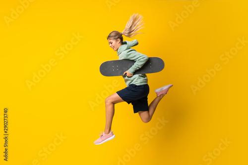 Valokuva Blonde teenager skater girl jumping over isolated yellow background