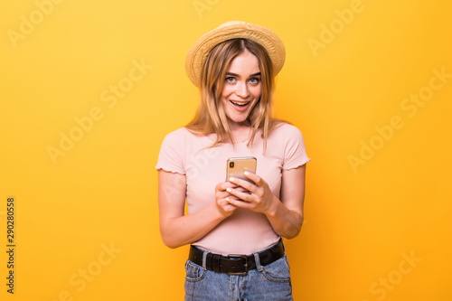 Pretty woman using smartphone over colorful orange background - 290280558