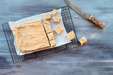 Block Of Delicious, Homemade Peanut Butter Fudge Being Cut Into Squares Over A Textured Wood Table Background With Old Knife. Image Shot From Above.