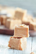 Squares of delicious, homemade peanut butter fudge over a rustic wood table. Selective focus on candy in the foreground with blurred background.