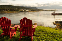 A Pair Of Adirondack Chairs At The Edge Of The Beach Overlooking The Ocean, On A Patch Of Green Grass, A Fishing Boat At The End Of The Dock In The Harbor And A Small Town In Front
