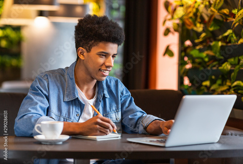 Obraz Young teen blogger making notes for new publication at cafe - fototapety do salonu