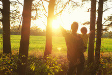 Father Holds His Toddler Son In His Arms And They Open Hands Togerher To Meet Beautiful Sunset On The Edge Of Forest. Father's Day, Happy Parenthood, Touching Family Moments.