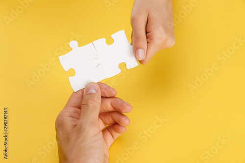 Fototapety, obrazy: cropped view of man and woman holding pieces of white puzzle on yellow background