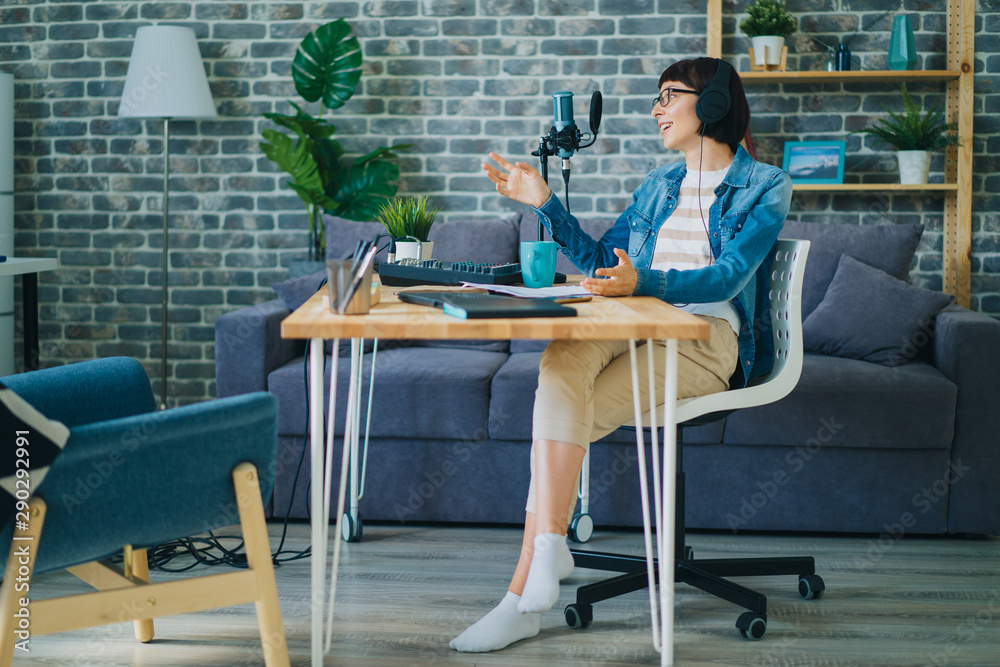 Fototapeta Cheerful young lady in glasses is talking recording audio using microphone in apartment enjoying communication and blogging activity. Youth culture and devices concept.