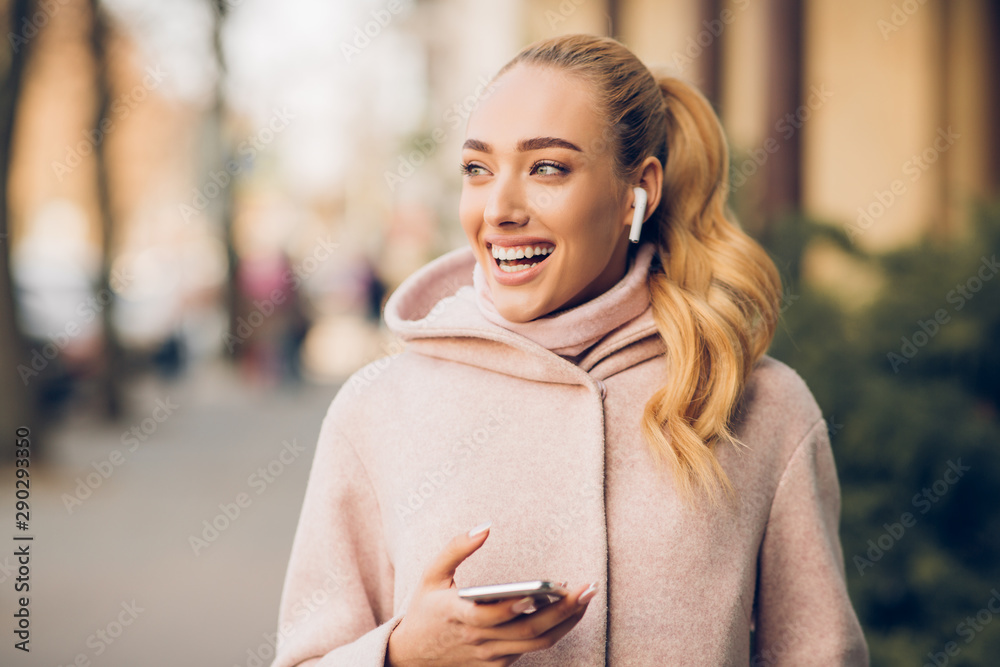 Fototapeta Stylish woman listening music on her airpods in city