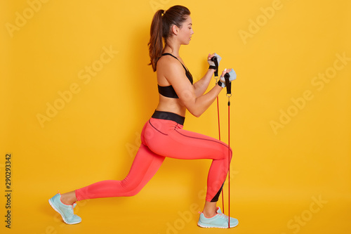 Fotografia Indoor shot of strong woman dressed black bra and leggins, using resistance band in her exercising at home, fitness model workout isolatedbover yellow background