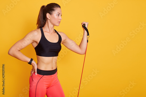 Close up portrait of beautiful athletic girl performs exercises using resistance band, young Caucasian girl pumping biceps isolatedover yellow background Fotobehang