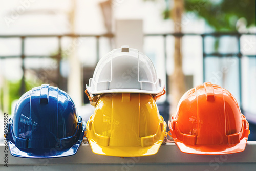 White, yellow and other colored safety helmets for workers' safety projects in the position of engineers or workers on concrete walls in the city Canvas Print