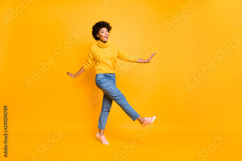 Fototapety, obrazy: Full length body size photo of cheerful black afro american woman dancing or moving forward wearing jeans denim yellow pullover sneakers isolated with vivid color yellow background