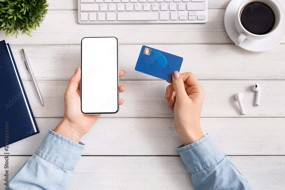 Fototapeta Woman using smartphone and credit card for online shopping
