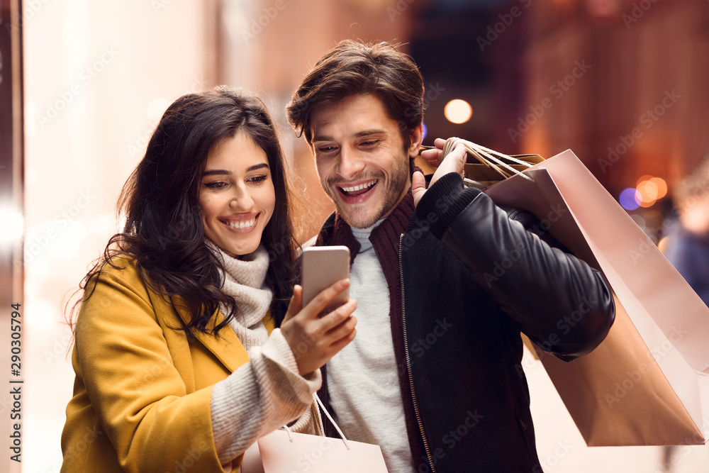 Fototapeta Order clothes online. Couple after shopping in mall using phone