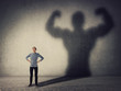 Brave teenager boy facing his fears as a powerful hero. Guy casting a strong muscular bodybuilder shadow, showing big biceps. Self defense, inner strength and motivation and confidence concept.