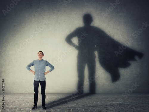 Fototapeta Casual teenage, keeps arms on hips smiling confident, casting a superhero with cape shadow on the wall