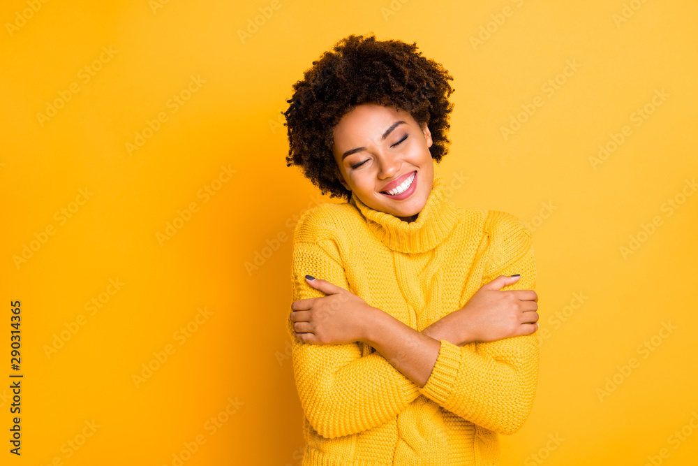 Fototapeta Photo of dark skin lady with closed eyes holding hands on shoulders wear warm knitted jumper isolated yellow background