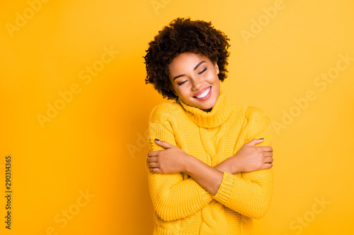 Photo  Photo of dark skin lady with closed eyes holding hands on shoulders wear warm kn