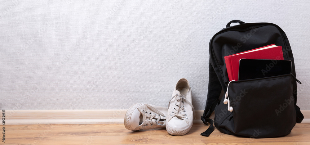 Fototapety, obrazy: Old white sneakers, book and tablet with earphones in backpack on wooden background. School and student travel concept