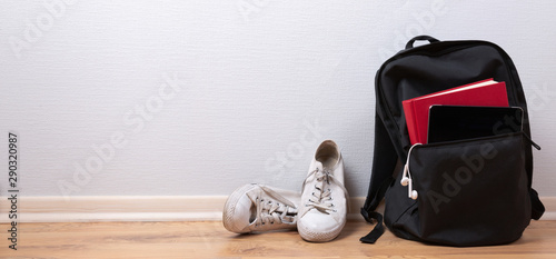Fototapeta Old white sneakers, book and tablet with earphones in backpack on wooden background. School and student travel concept obraz