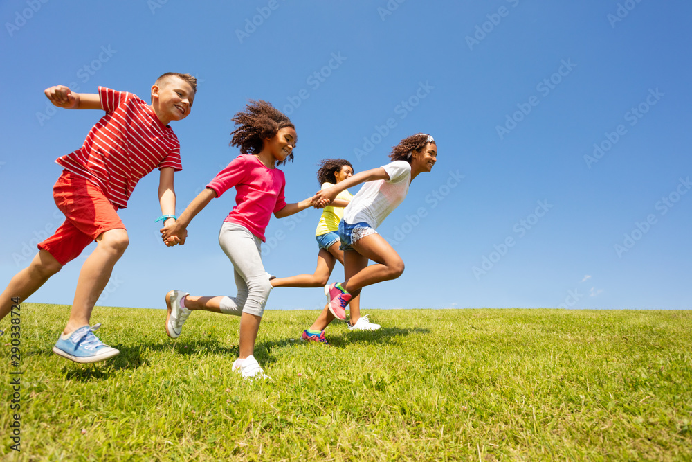 Fototapety, obrazy: Diverse group of happy kids run in park hold hands