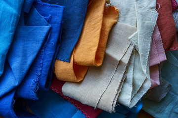 A stack of colorful fabrics background. Multicolored linen fabric