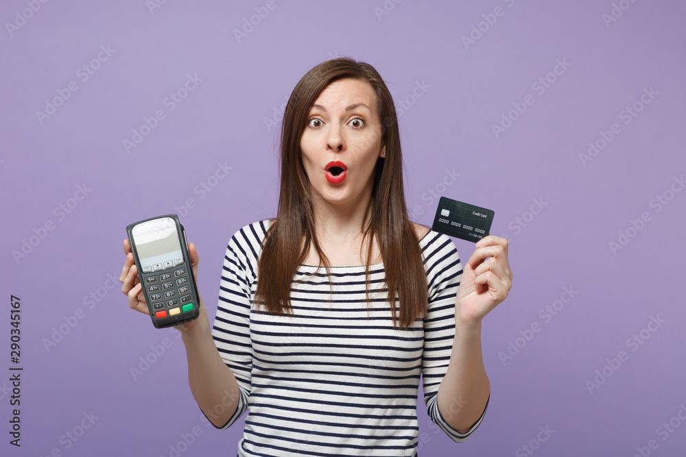 Fototapeta Woman in casual clothes isolated on violet background studio portrait. People lifestyle concept. Mock up copy space. Hold wireless modern bank payment terminal to process acquire credit card payments.