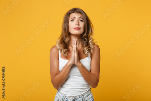 Pleading young woman girl in light casual clothes posing isolated on yellow orange background in studio Slika na platnu