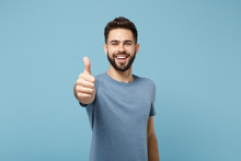 Young Smiling Cheerful Handsome Man In Casual Clothes Posing Isolated On Blue Wall Background, Studio Portrait. People Sincere Emotions Lifestyle Concept. Mock Up Copy Space. Showing Thumb Up.