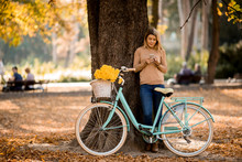 Young Woman With Bicycle Using...