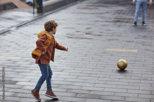 Six year old boy playing football in a city park with an adult