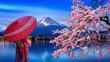 Leinwanddruck Bild - Asian woman wearing japanese traditional kimono at Fuji mountain and cherry blossom, Kawaguchiko lake in Japan.