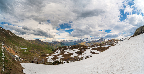 Fototapeta  Panorama of alpine valley and mountains in spring with large snowfield in the fo
