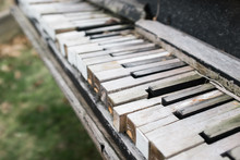 A Close-up Of A Worn Piano Keyboard That Has Been Left Outside.