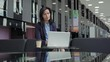 Tracking medium shot of middle aged businesswoman in suit sitting at table in office building or airport lobby and typing on laptop computer