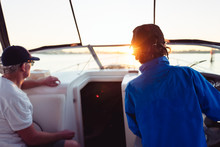 Father Teaching Son To Skipper A Motor Boat
