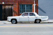 An Old Beat Up White Car Parked In An Urban Factory Zone