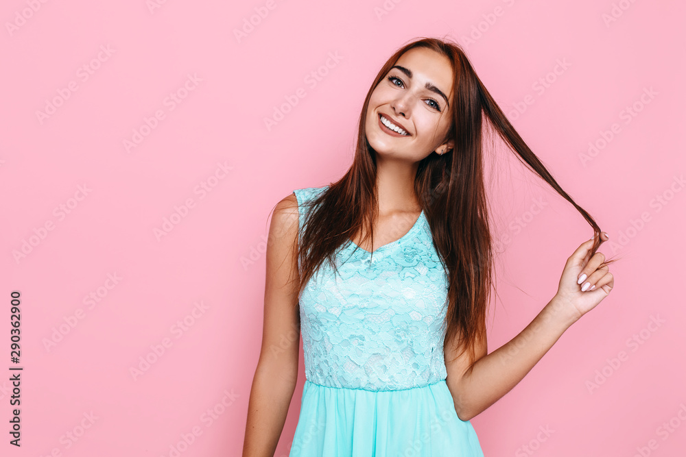 Fototapeta young girl, in a bright dress, smiling and posing on a pink background