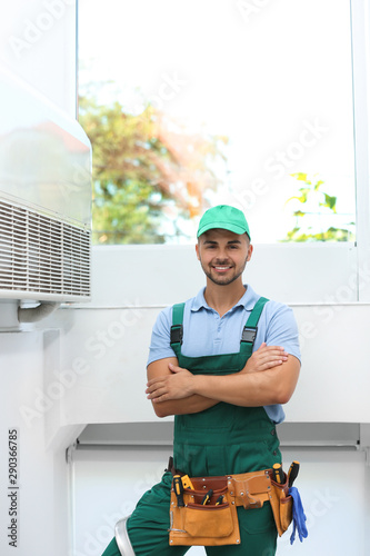Fotografía  Professional technician near modern air conditioner indoors