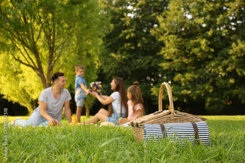 Foto  Picnic basket and happy family on background in park